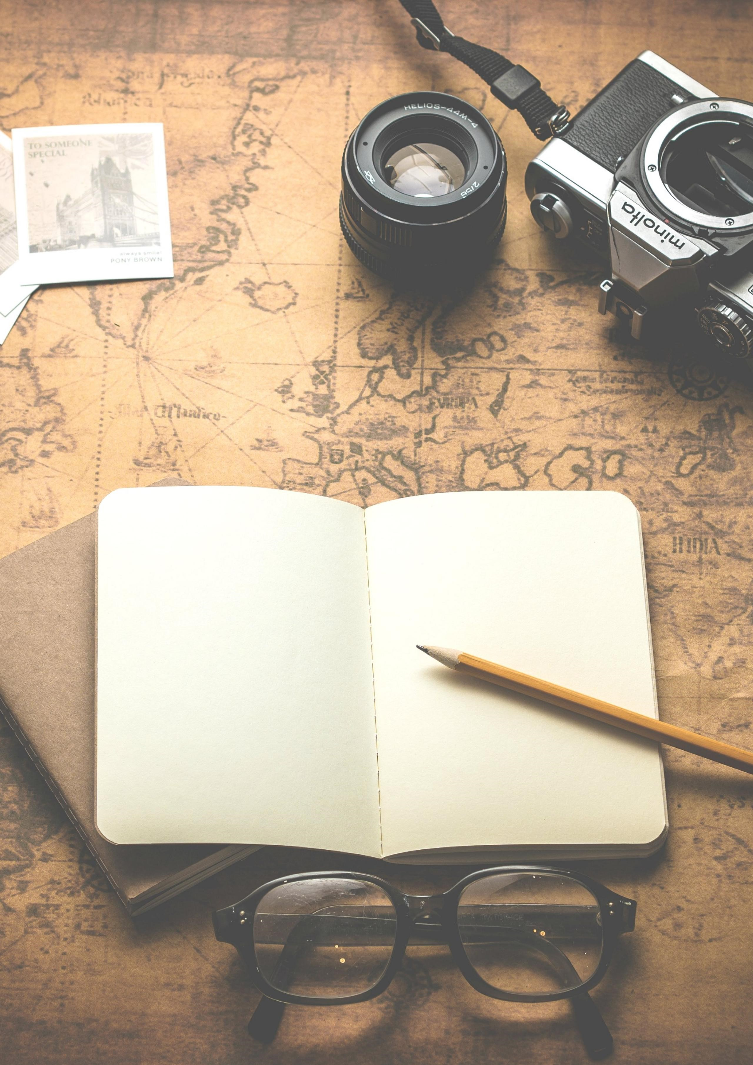 Travel essentials with a notebook, pen, camera and glasses. 3 Simple Ways Minimalism Can Help Your Life Abroad