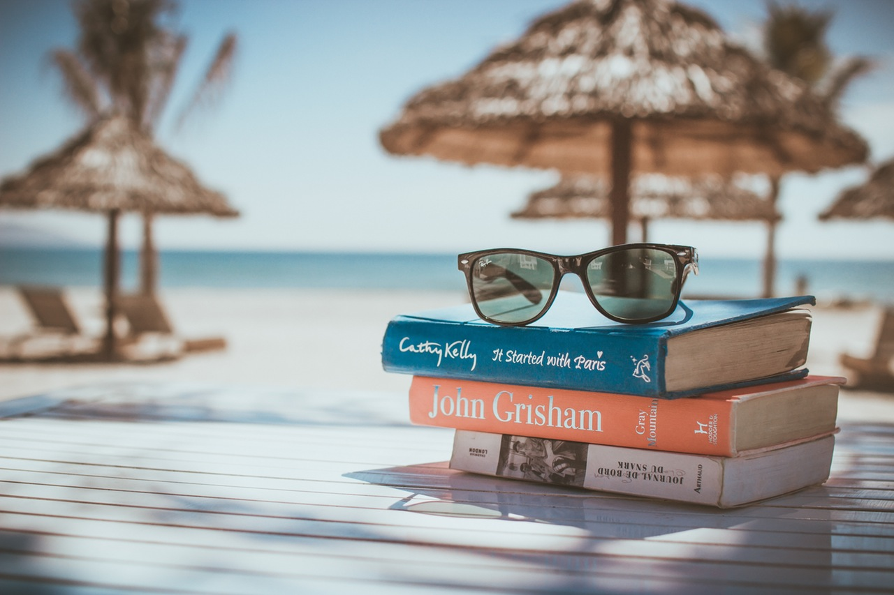 Background beach with books and sunglasses. 3 Simple Ways Minimalism Can Help Your Life Abroad