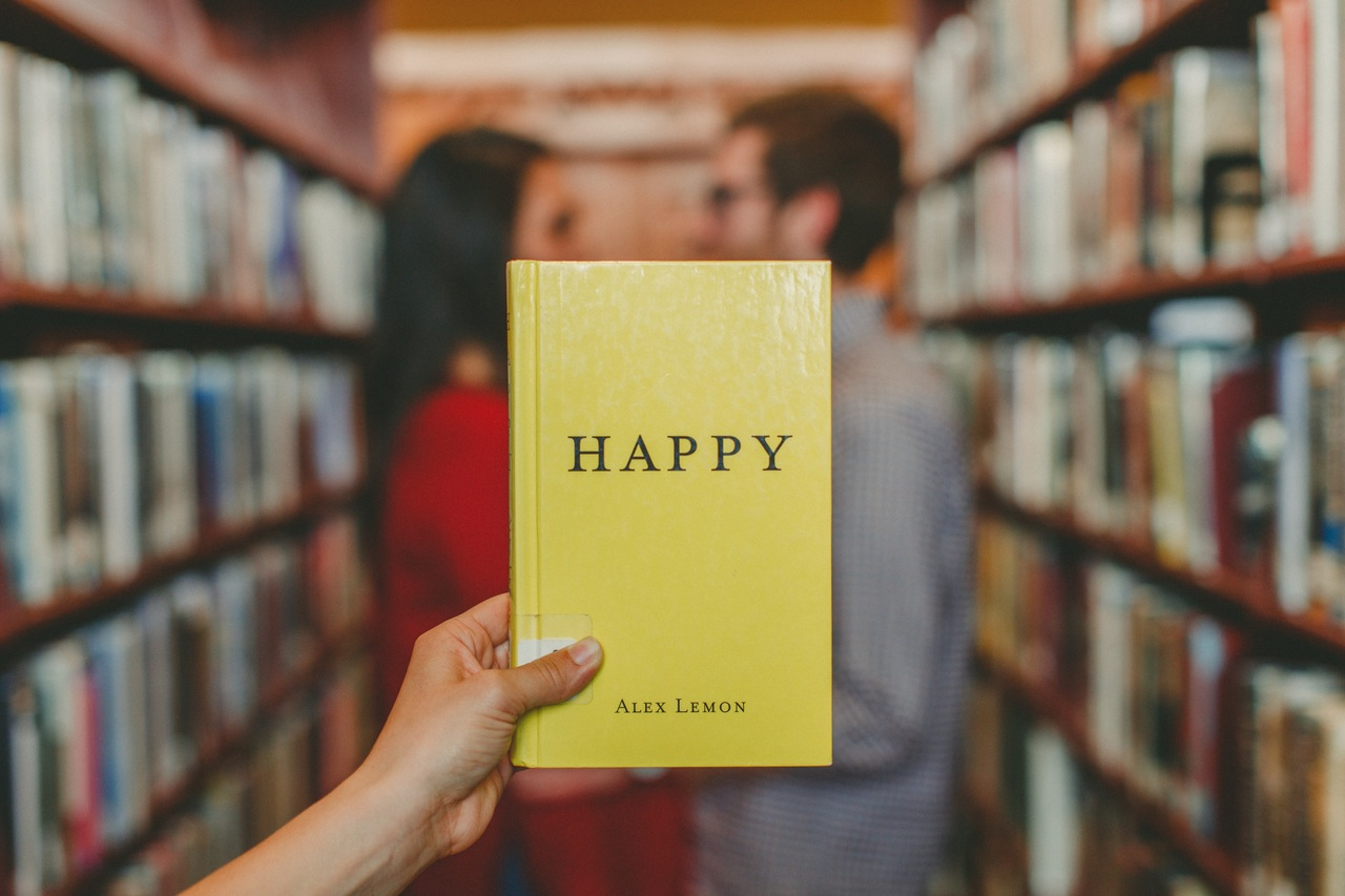 blurry couple in a library with a focus on the book with 'happy' title. 3 Simple Ways Minimalism Can Help Your Life Abroad